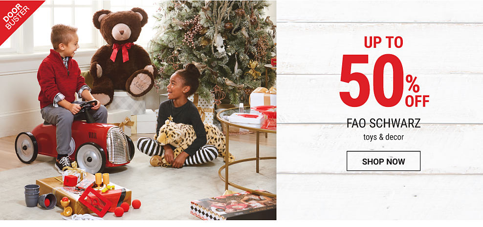 A boy & a girl playing with toys beside a Christmas tree. DoorBuster. Up to 50% off FAO Schwarz toys & decor. Shop now.