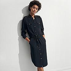 A woman wearing a black button front long sleeved dress. Shop dresses.
