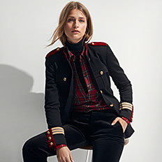 A woman wearing a black jacket over a red button front blouse & black pants. Shop tops.