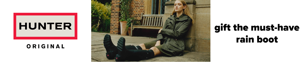 A woman wearing an olive green overcoat & black tall boots. Hunter Original. Gift the must have rain boot. Shop now.