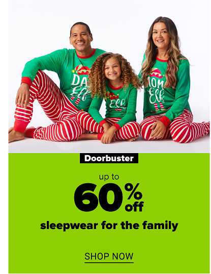 A family of three wearing matching elf-themed pajamas featuring festive green tops with red accents and candy cane-striped pajama pants. Doorbuster. Up to 60% off sleepwear for the family. Shop now.