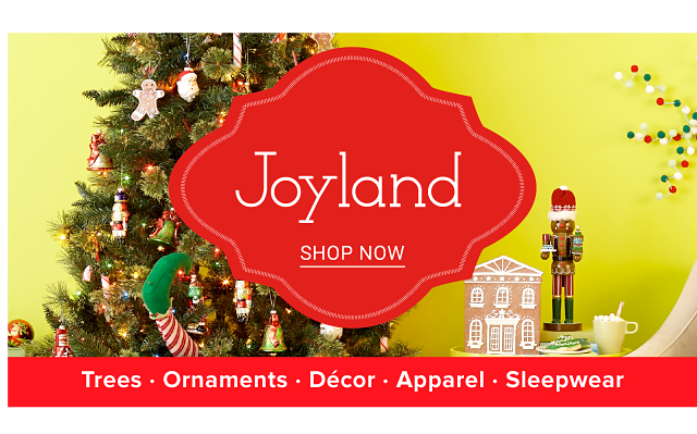 A fully decorated Christmas tree surrounded by holiday decor. Joyland. Trees. Ornaments. Decor. Apparel. Sleepwear. Shop now.