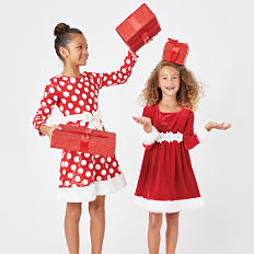 Two girls wearing red and white holiday dresses and holding gifts. Shop Dresses.