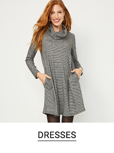 A woman in a long sleeve, gray sweater dress. Shop dresses.