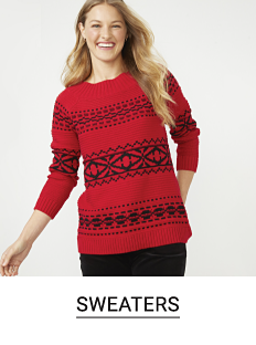 A woman in a red and black printed sweater and black pants. Shop sweaters.