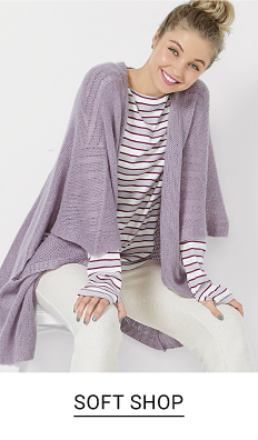 A young woman in a white and lavendar stripe long sleeve top and a long lavender cardigan. Shop soft shop.
