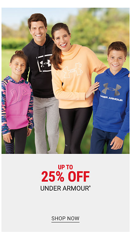 A girl wearing a fuchsia hoodie with multi colored sleeves & black pants standing next to a man wearing a black hoodie with a white Under Armour logo & gray pants, a woman wearing a light orange long sleeved top with a white Under Armour logo & black pants & a boy wearing a blue hoodie with a gray Under Armour logo & navy pants. Up to 25% off Under Armour. Shop now.
