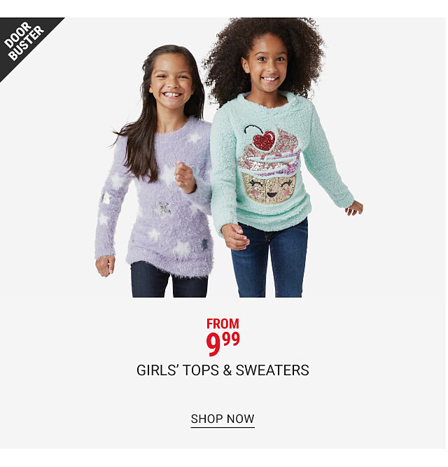 A girl wearing a purple sweater with white stars, navy pants & gray boots standing next to a girl wearing am light blue sweater with a multi colored smiling cupcake front graphic, blue jeans & beige boots. From $9.99 girls tops. Shop now.