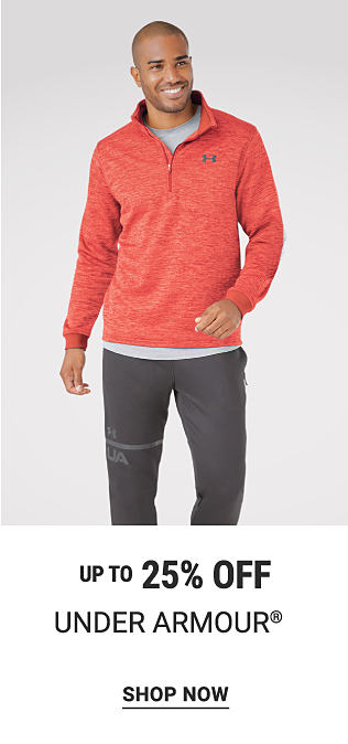 A man wearing a coral quarter zip fleece over a gray shirt & dark gray pants. Up to 25% off Under Armour. Shop now.