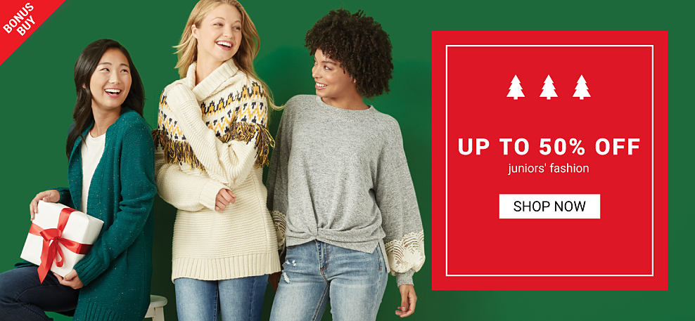 A woman wearing a long open front green sweater over a white top and navy pants standing next to a woman wearing a white cowl neck sweater with a brown & yellow patterned print & blue jeans & a woman wearing a gray sweater & blue jeans. Bonus Buy. Up to 50% off juniors fashion. Shop now.