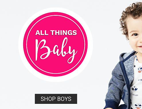 A baby boy wearing a gray hoodie over a white shirt with an all over print sitting next to a baby girl wearing a frilly pink hoodie over a navy top with white dots. All Things Baby. Shop boys.