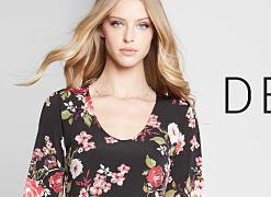 A woman wearing a black dress with a multi colored floral print. A woman wearing a short sleeved black dress. A woman wearing a multi colored print long jacket & blue jeans. Designer Shop. Shop dresses.