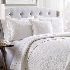 A bed with a white quilt and pillows to match. Shop quilts.