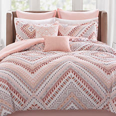 A bed with a white, coral, and gray printed comforter with pillows to match. Shop bed-in-a-bag sets.