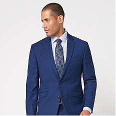A man wearing a blue suit, a white dress shirt & a gray tie. Shop suits.