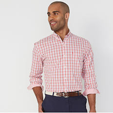 A man wearing a red, white & blue check long sleeved button front shirt & navy shorts. Shop casual shirts.