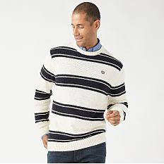 A man wearing a white & black horizontal striped sweater & blue jeans. Shop sweaters.
