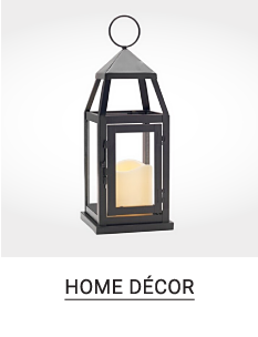A decorative lantern with a white candle. Shop home decor.