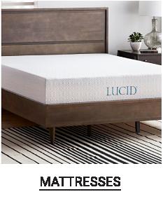 A white mattress on a bed frame. Shop mattresses.