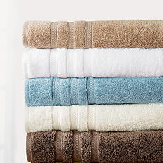 A stack of folded towels in a variety of colors. Shop bath.