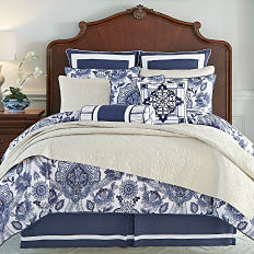 A bed with a printed comforter and pillows to match. Shop designer bedding.