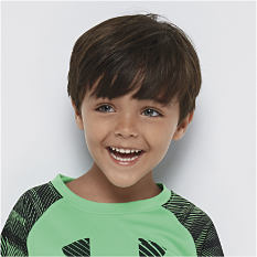 A boy wearing a green & black shirt. Shop ages 5 - 7.