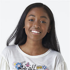 A girl wearing a white shirt with a multi-colored print. Shop ages 8 & up.