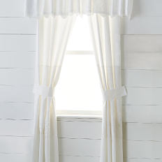 A window with white curtains. Shop window treatments.