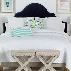 A bed with a white bedspread and pillows to match. Shop bed and bath.