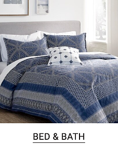 A blue and off white patterned bedding set with matching pillows and a small decorative pillow. Bed and bath.