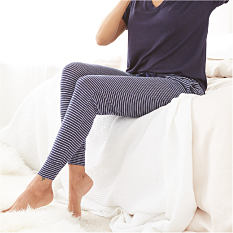 A woman wearing a navy short sleeved pajama top & navy & white horizontal striped pajama pants. Shop bottoms.
