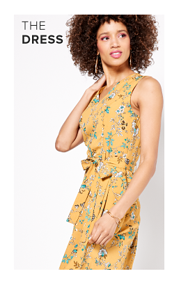 A woman in a yellow sleeveless floral blouse. The dress.