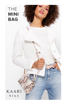 A woman in a white top, white jacket and jeans and carrying a small snakeskin print bag. The mini bag. Kaari Blue.