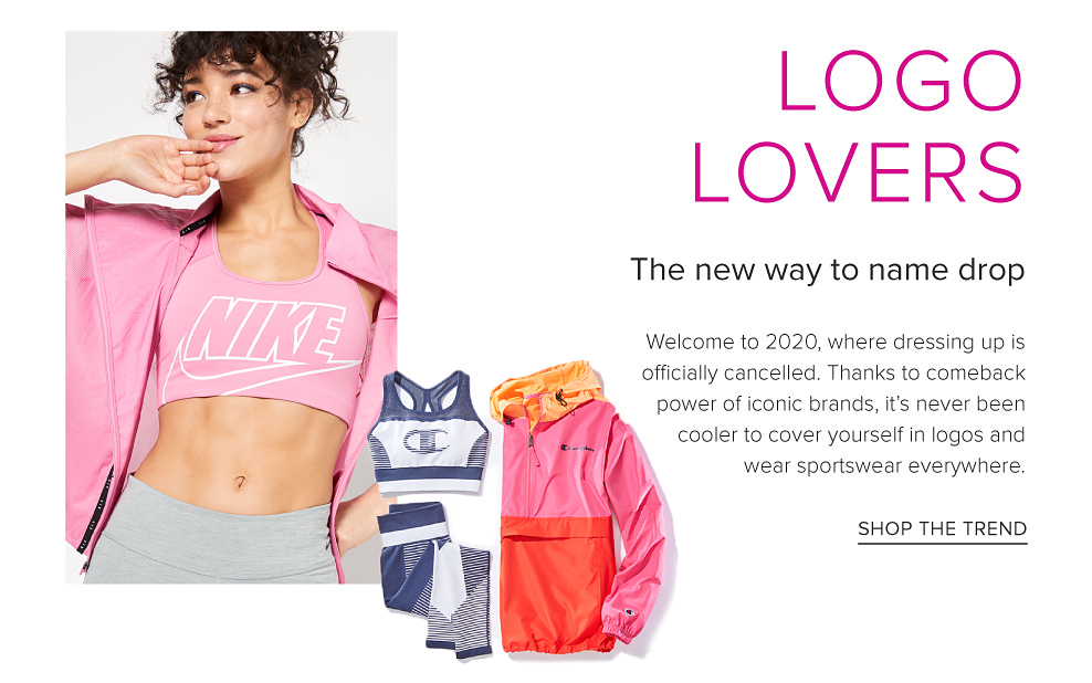 A woman in a light pink Nike logo sports bra, a light pink unzipped jacket and gray tights. A pink, orange and red colorblock Champion hoodie next to a blue and white Champion Sportsbra and tights to match. Logo lovers. The new way to name drop. Welcome to 202, where dressing up is officially cancelled. Thanks to comeback power of iconic brands, it's never been cooler to cover yourself in logos and wear sportswear everywhere. Shop the trend.