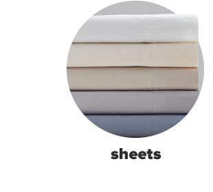 A stack of bed sheets in various colors featuring white, pale blue and more. Sheets.