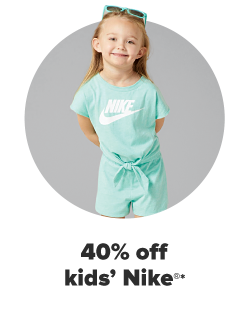 A girl wears a seafoam green Nike jumper, with a built-in belt tied at the waist. She has matching green sunglasses. 40% off kids' Nike.