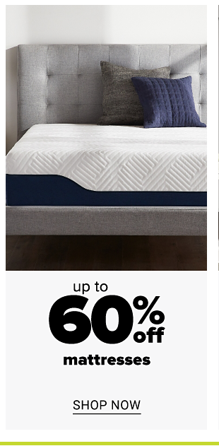 A white mattress on a bed with a grey headboard, a grey pillow and a navy pillow. Up to 60% off mattresses. Shop now.