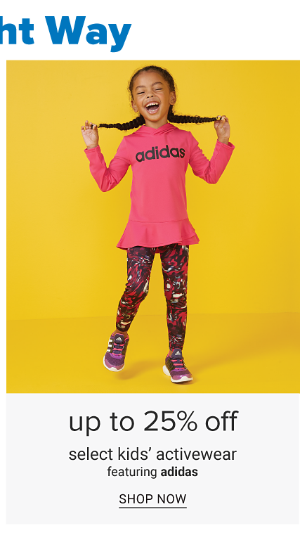 A girl wearing a fuchsia long sleeved top with a black adidas logo front graphic, multi colored print leggings & navy sneakers. Up to 25% off select kids activewear featuring adidas. Shop now.