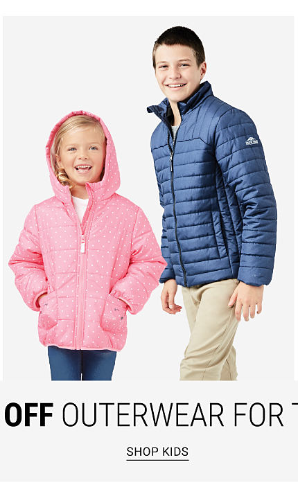A girl wearing a pink hooded winter coat over a white top & blue jeans standing next to a boy wearing a blue puffer coat & beige pants. Shop kids.