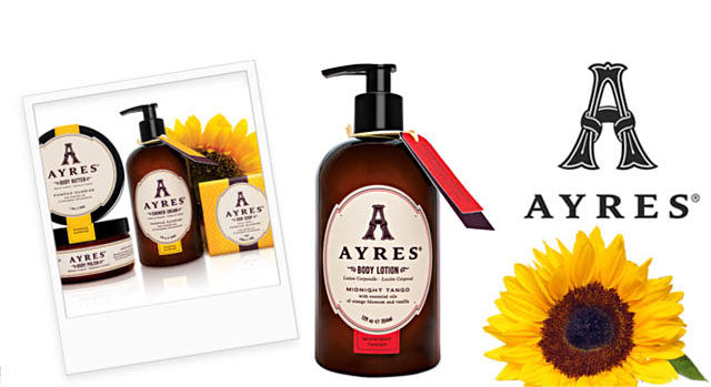 A Polaroid picture of Ayres skin care products. A pump bottle of Ayres body lotion next to a sunflower.  Ayres. An all-natural aromatherapy body care collection infused with pure essential oils & a Latin touch, creating a unique experience for everyone who is passionate about life. Shop Ayres.