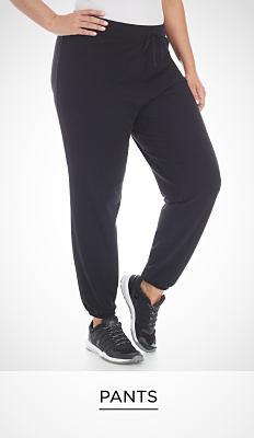 A woman wearing a white T-shirt, black workout pants & black sneakers. Pants. Shop now.