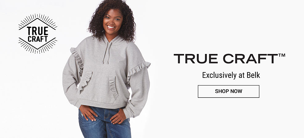 A young woman wearing a gray hoodie with frilly accents & distressed blue jeans. True Craft. Exclusively at Belk. Shop now.