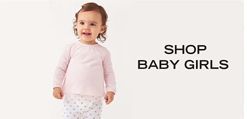 A baby girl wearing a ligh pink top & white pants with red dots. Shop baby girl.