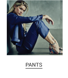 A woman in a blue jacket, floral high heel sandals and cropped pants to match. Shop pants.