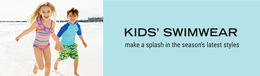 A girl wearing a multi colored horizontal striped 1 piece swimsuit running on the beach next to a boy wearing a light blue T shirt with dark blue sleeves & a green, blue & teal print swim trunks. Kids? swimwear. Make a splash in the season?s latest styles.