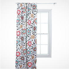 A white curtain with bright pink and teal flowers hangs from a window. Shop window treatments.