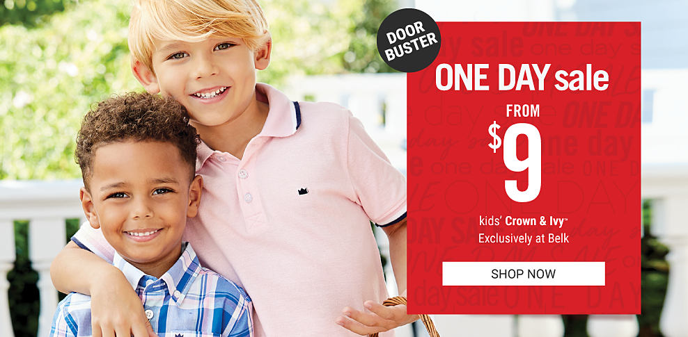 A boy wearing a blue, white & pink plaid short sleeved button front shirt standing next to a boy wearing a light pink polo. One Day Sale. Doorbuster. From $9 kids Crown & Ivy. Exclusively at Belk. Shop now.