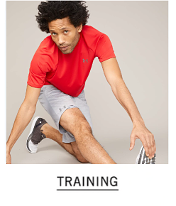 A man in a red t-shirt, gray shorts and sneakers. Shop training.
