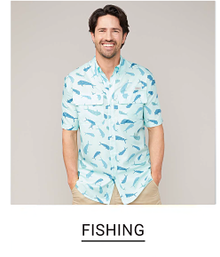 A man in a white and green print short sleeve button front shirt and khakis. Shop fishing apparel.