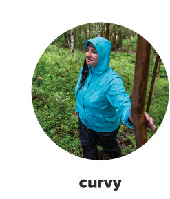 A woman in a blue rain jacket and black pants. Curvy.